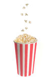 Popcorn falling into a classic striped bucket Royalty Free Stock Photo