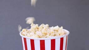 Popcorn falling in striped red and white bucket on gray background. Popcorn falling in striped red and white bucket  on gray background stock footage