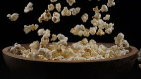 Popcorn falls into a wooden bowl