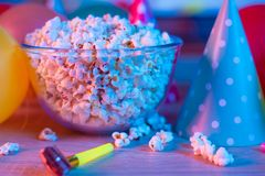 Popcorn with festive accessories on the background of TV. Watching TV on the occasion of a family celebration or in a circle of. Friends. Color and sevremenny stock image
