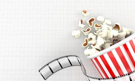 Popcorn with film strip. On blank sheet of paper Royalty Free Stock Images
