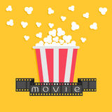 Popcorn. Film strip ribbon. Red yellow box. Cinema movie night icon in flat design style. Yellow background. Stock Image