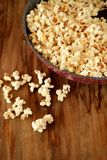 Popcorn in a frying pan. On a wooden table Royalty Free Stock Images