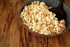 Popcorn in a frying pan. On a wooden table Stock Photo