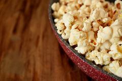 Popcorn in a frying pan. On a wooden table Stock Image