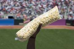 Popcorn at the Game. A vender holds up a bag of popcorn Royalty Free Stock Photography