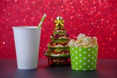 Popcorn, Getränk und Weihnachtsbaumdekoration für Film auf rotem bokeh Hintergrund, selektiver Fokus stockfotografie