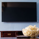 Popcorn in glass bowl and remote control Stock Photo