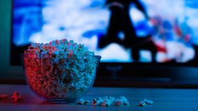 Popcorn in a glass plate on the background of the TV. Color bright lighting, blue and red. Background royalty free stock photo