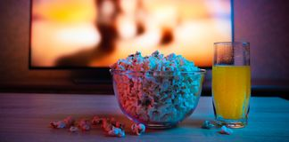 Popcorn in a glass plate with a drink on the background of the TV. Color bright lighting. Background stock image