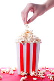 Popcorn and hand on isolated background Royalty Free Stock Photography