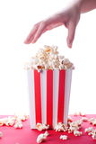 Popcorn and hand on isolated background Royalty Free Stock Photo