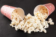 Popcorn horizontal banner. Red stripped paper cup and kernels lying on dark background. Copy space. Royalty Free Stock Image