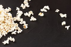 Popcorn horizontal banner. Red stripped paper cup and kernels lying on dark background. Copy space. Royalty Free Stock Images