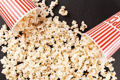 Popcorn horizontal banner. Red stripped paper cup and kernels lying on dark background. Copy space. Stock Photos