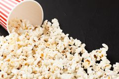 Popcorn horizontal banner. Red stripped paper cup and kernels lying on dark background. Copy space. Stock Photography