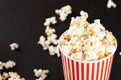 Popcorn horizontal banner. Red stripped paper cup and kernels lying on dark background. Copy space. Stock Image
