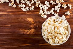 Popcorn horizontal banner. Red stripped paper cup and kernels lying on dark brown wooden background. Copy space. Top view. Royalty Free Stock Photography