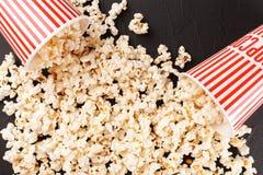 Popcorn horizontale banner Rode gestripte document kop en pitten die op donkere achtergrond liggen De ruimte van het exemplaar Stock Foto's