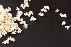Popcorn horizontale banner Rode gestripte document kop en pitten die op donkere achtergrond liggen De ruimte van het exemplaar Royalty-vrije Stock Afbeeldingen
