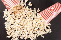 Popcorn horizontale banner Rode gestripte document kop en pitten die op donkere achtergrond liggen De ruimte van het exemplaar Stock Foto