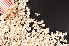 Popcorn horizontale banner Rode gestripte document kop en pitten die op donkere achtergrond liggen De ruimte van het exemplaar Stock Fotografie