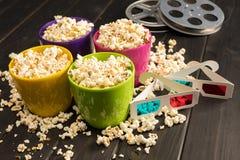 Popcorn i bunkar och exponeringsglas 3D på tabellen, begrepp för filmtid Arkivbild