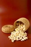 Popcorn i bunke isolerad röd bakgrund Royaltyfri Foto