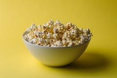 Popcorn i bunke på gul bakgrund, mellanmålmat arkivfoto