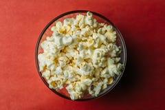 Popcorn i bunke på röd bakgrund, mellanmålmat, bästa sikt arkivfoto