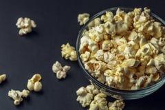 Popcorn i den glass bunken på mörk bakgrund, kopieringsutrymme royaltyfri bild