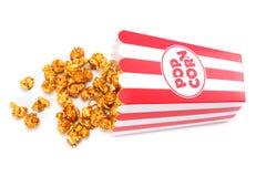 Popcorn i den randiga hinken som isoleras på vit fotografering för bildbyråer