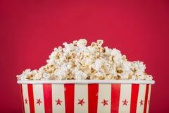 Popcorn i den retro asken som isoleras på röd bakgrund royaltyfri fotografi