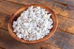 Popcorn i den trevliga träbunken för Wathcing filmer på Wood Backgrou Arkivbild
