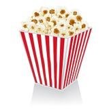 Popcorn i en ask på en vit bakgrund Royaltyfri Foto