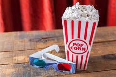 Popcorn i klassiska bioportionask och exponeringsglas 3D för Wathcin Royaltyfri Bild