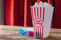 Popcorn i klassiska bioportionask och exponeringsglas 3D för Wathcin Fotografering för Bildbyråer