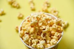 Popcorn i koppbunke och gult popcorn f royaltyfria foton