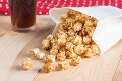Popcorn i påse och cola på tabellen fotografering för bildbyråer