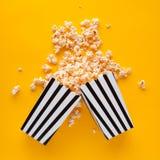 Popcorn i papperspåsen spridd på bästa sikt för gul bakgrund royaltyfria bilder