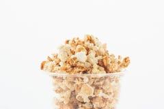 Popcorn i plast- kopp på vit bakgrund Royaltyfri Fotografi