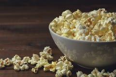 Popcorn i platta på tabellen, kopieringsutrymme royaltyfria bilder