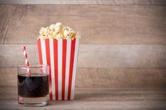 Popcorn i röd och vit papp med sodavatten på trätabellen arkivbild