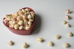 Popcorn i röda hjärtor formar bunken arkivfoton