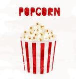 Popcorn i randig hink på vit bakgrund Arkivfoto