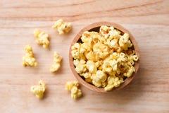 Popcorn i träbästa sikt för bunke- och träbackgroubd/sött smörpopcorn saltar fotografering för bildbyråer