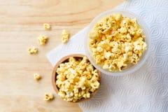 Popcorn i tr?b?sta sikt f?r koppbunke- och tr?backgroubd/s?tt sm?rpopcorn saltar royaltyfri bild