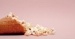 Popcorn in ice cream cones on pink background