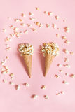 Popcorn in ice cream cones on pink background. Top view. Stock Photos