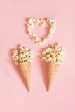 Popcorn in ice cream cones on pink background. Top view. Stock Image
